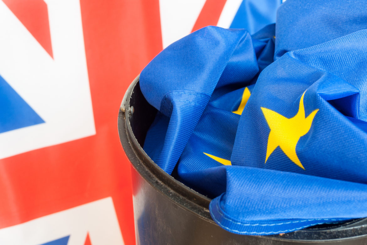 Flag of European Union in Dustbin with the Flag of the UK in background